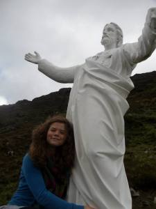 Jennifer Ashwell poses with a statue of Jesus sitting atop a mountain in Ireland.